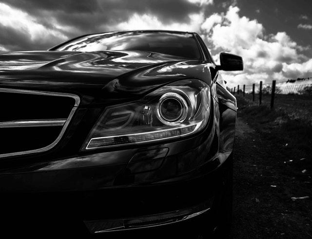 černobílá fotografie automobilu zepředu, záběr na světlo