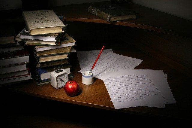 plný stůl knih a napsaný dopis